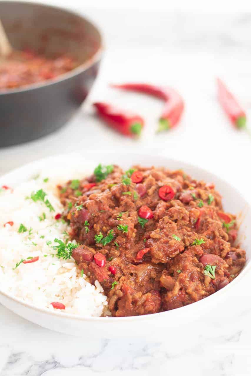 Close up of chilli con carne in a bowl with sprinkled parsley and chopped chilli