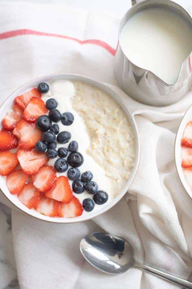 porridge oats with strawberries, blueberries, yogurt and jug of milk